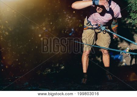 Young Climber Hanging On A Rock On A Rope And Looks Somewhere On The Wall. Extreme Lifestyle Outdoor Activity Concept