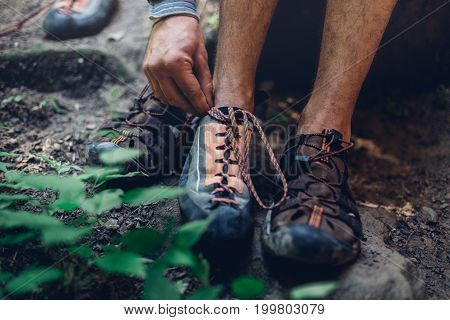 Unrecognizable Man Dresses Climbing Shoes For Climbing. Extreme Hobby Outdoor Activity Concept