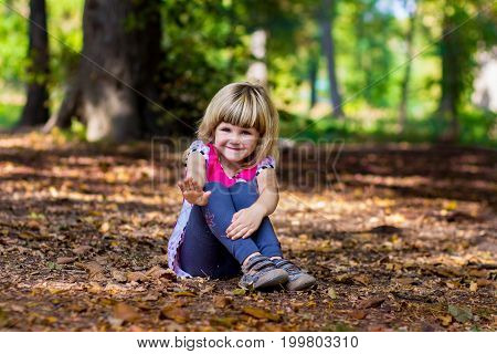 Adorable smiling little girl sitting in a park on yellow leaves and greeting waving her hand