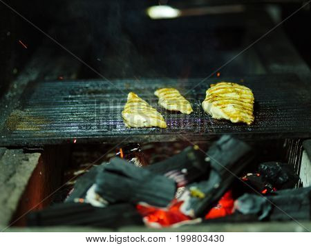Close-up of delicious juicy pieces of grilled chicken. Nutritious meat on a blurred grid background. Tender smoky fillet with firewood. Outdoors, nature, cooking concept. Copy space.