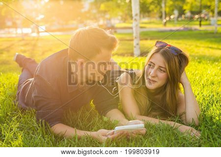 Sunny portrait of sweet young couple lying relaxing on the grass together listens to music in earphones on smartphone, summer day