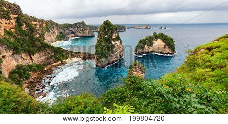 Sea coast view with little house standing on the high cliff bring above sea and little rocky islets. Atun beach Nusa Penida island. Popular travel destination on Bali holidays. Indonesian background.