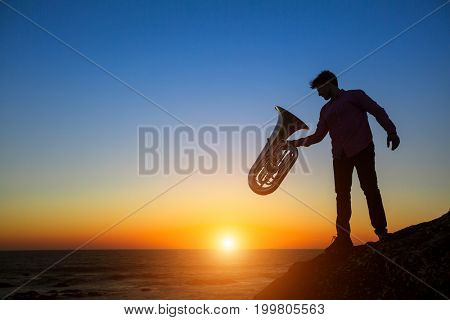 Silhouette of musician with Tuba instrument on rocky sea coast during amazing sunset.