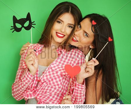 two stylish sexy hipster girls best friends ready for party, over green background
