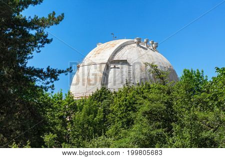 Giant white dome of the reflecting telescope covered with rust at the Observatory among the trees
