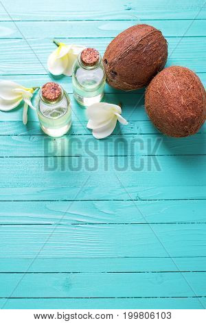Bottles with coconut oil on bright wooden background. Selective focus. Place for text. Vertical image.