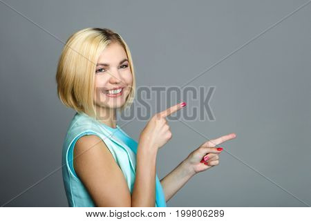 Beautiful woman points with fingers