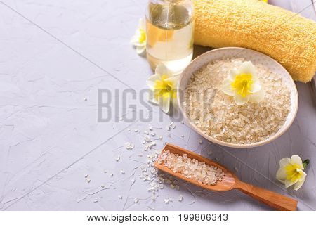Spa setting in yellow color. Bottle with aroma oil sea salt in bowl towel and flowers on grey textured background. Selective focus. Place for text.
