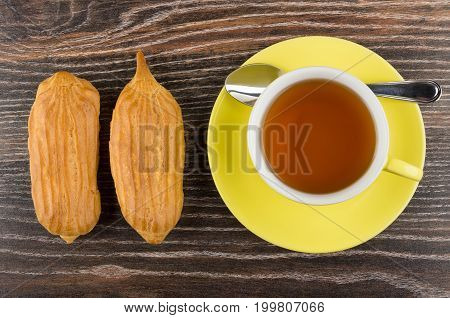 Cup Of Tea, Two Eclairs On Dark Wooden Table