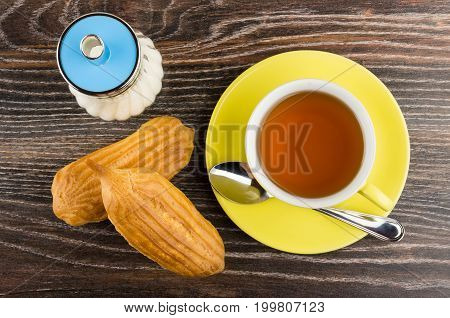 Cup With Tea, Teaspoon, Sugar And Two Eclairs On Table