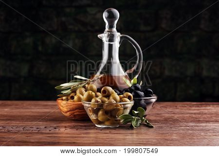 Bottle Virgin Olive Oil And Oil In A Bowl With Some Olives