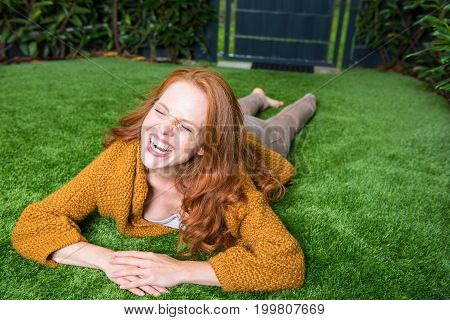 Beautiful red-haired woman lies on the lawn and takes pleasure in her garden