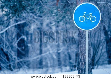 Image of winter landscape with road sign of bike path in frost