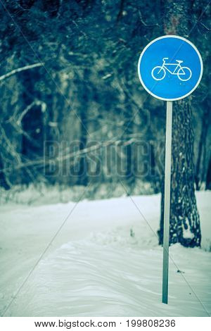 Picture of winter day with trees with road sign of bicycle path in frost. Toned photo