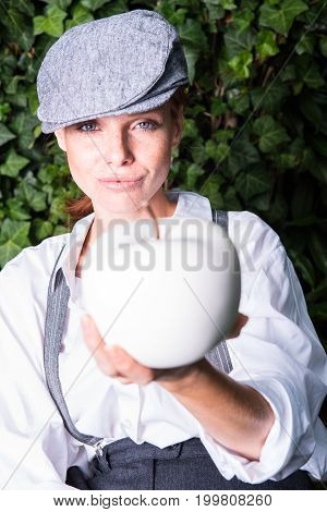 red-haired woman with cap in the garden offers apple