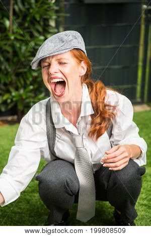 young red-haired woman as a man dressed in the garden