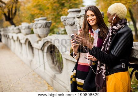 Two Young Pretty Multiracial Girlfriends At Autumn Day