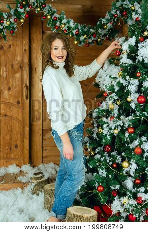 Beautiful woman in new year interior dresses up Christmas tree.