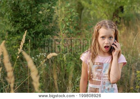 A beautiful girl is standing in a pink T-shirt in the park and talking on the phone. Sunset. She has a surprised slightly frightened face