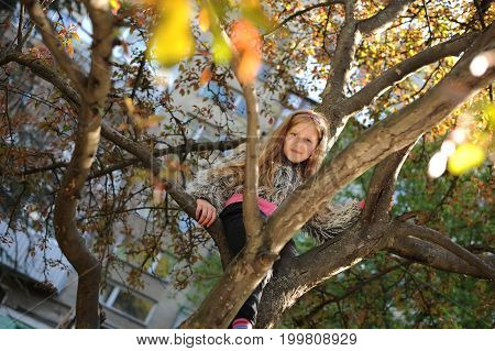 The girl sits on a tree and smiling. The girl is 9 years old