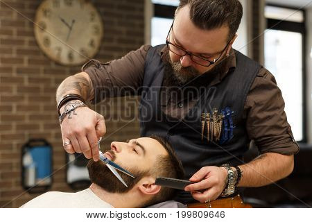 Barber make beard haircut with scissors in barbershop. Hairstyle in barbershop.