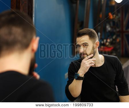 Man look at haircut by hairstylist at barbershop. Stylish barber and client in mirror
