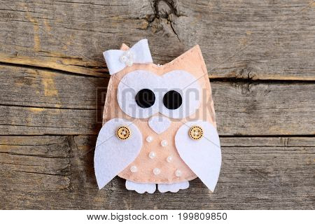 Cute felt owl isolated on an old wooden background. Owl decor made of felt and decorated with buttons and beads. Beautiful felt decor. Closeup