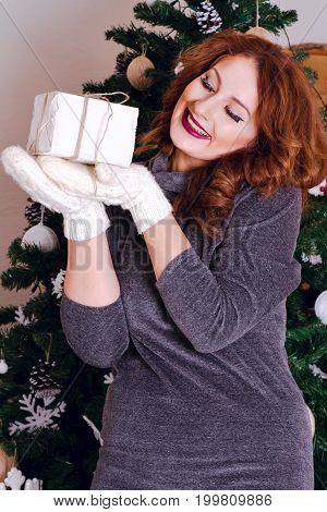 Beautiful woman enjoys gift to have dressed up Christmas tree