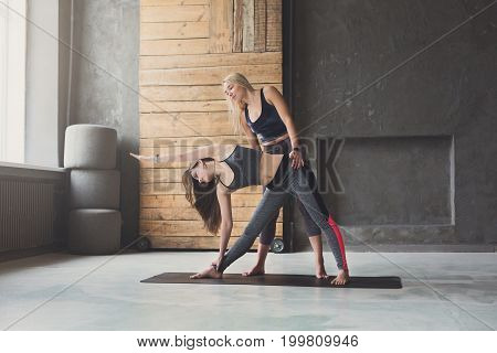Yoga class instructor and beginner making asana exercises. Teacher assists to make triangle pose, trikonasana. Healthy lifestyle in fitness club. Stretching with coach