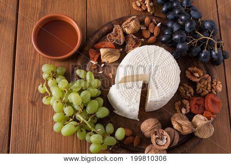 Cheese platter with fruits, homemade indian paneer cheese on wooden board with grapes and nuts, top view
