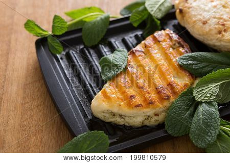 Halloumi roasted on grill cypriot cheese served with mint on wooden desk, close-up, selective focus