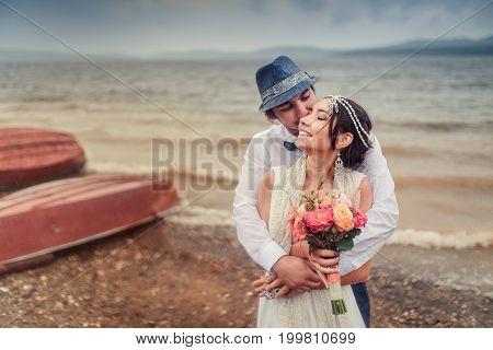 Boho wedding. couple kissing on the coast