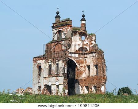 The old ruined Church. Ruins on the background of blue sky. Green grass field