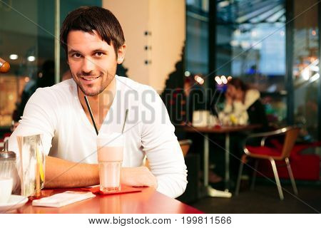 good-looking single guy sitting in a cafe, enjoying some coffee