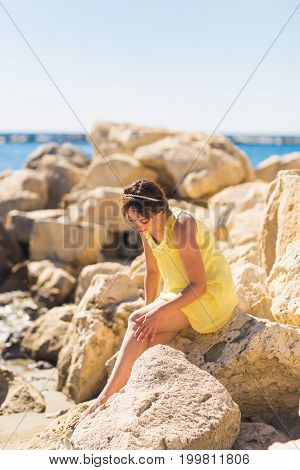 Beautiful girl relaxing and smiling outdoor at summer beach.