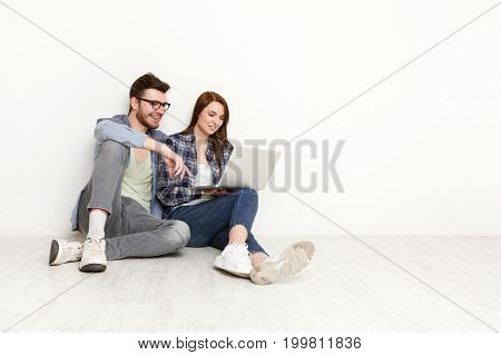 Couple conversation with laptop. Woman showing new dress to man on computer, he smiles in approval, white background, studio shot