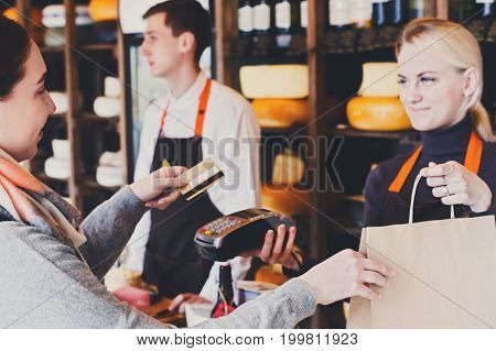 Customer paying with credit card for order of cheese in grocery shop. Retail, payment service.