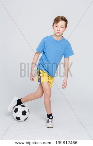Young football player posing on camera. Handsome boy in sportswear doing tricks with soccer ball over white studio background. Active and sporty lifestyle concept. Vertical, copy space