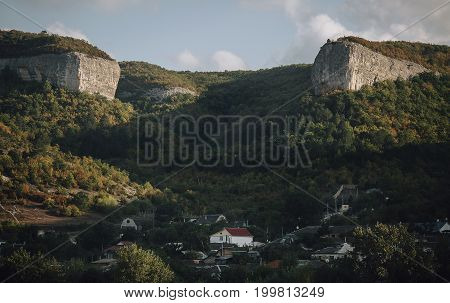Two stone mountains over village in green forrest under white clouds