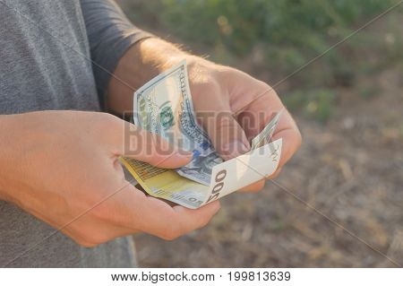 Man in grey turtleneck holds in his arms banknotes of dollar and euro