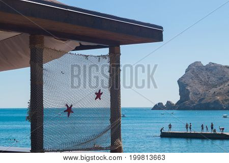 View at the part of balcony decorated with a fishnet with starfishes. Sea with mountain and pier with peoples on the background. Sudak Crimea
