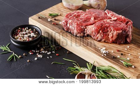 Raw rib eye steak with herbs and spices closeup. Cooking ingredients for restaurant dish. Fresh meat, pepper salt, rosemary and garlic on wooden board at black. Stylish food background