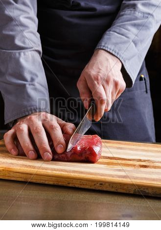 Man cutting filet mignon on wooden board at restaurant kitchen. Chef preparing fresh meat for cooking. Modern cuisine backgroung with copy space, vertical