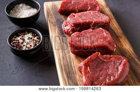 Raw filet mignon steaks with spices closeup. Slices of fresh beef meat arranged in a row on wooden cutting board and spices at black slate background