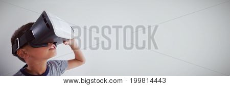 Schoolboy using virtual reality headset against white background