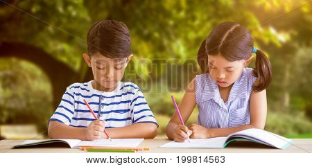 Children writing on books at table against trees and meadow in the park