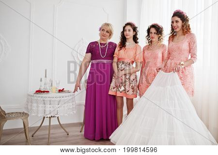 Bridesmaids And Mother Looking At Bride While She Is Dressing Up.