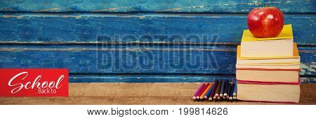 Back to school text over white background against apple with stacked books and pencils on table