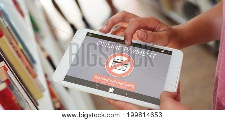 Online payment text on phone screen against schoolboy using digital tablet in library