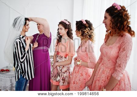 Bridesmaids And Mother Helping Bride To Dress Up And Get Ready For Her Wedding.
